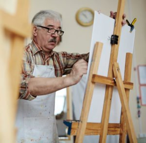 Man painting on an easel