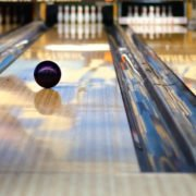 Swirling bowling ball is rolling down the path to the bowling pins