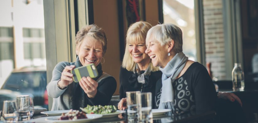 Group of older women looking at cellphone